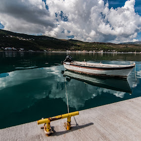 by Grigoris Koulouriotis - Transportation Boats ( clouds, water, sky, blue, greece, reflections, sea, boat,  )