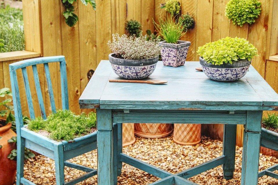 Petit espace extérieur meublé par une table et deux chaises de jardin en teck bleu ainsi qu'une chaise