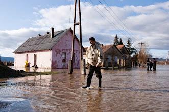Photo: Ipolytarnóc, 2009. december 26.Egy férfi sétál gumicsizmában a vízzel borított úttesten egy családi ház előtt a Nógrád megyei Ipolytarnócon, miután az Ipoly kilépett medréből a hajnali órákban; a településen 27 embert kellett kimenekíteni otthonából. Az áradás miatt nyolc ház van veszélyben, amelyből négyet körbevesz a víz, négynek pedig a kertjén folyik keresztül. Az éjszaka kimenekített 27 embert az önkormányzat, illetve a katasztrófavédelem a helyi óvodában helyezte el, ellátásukat biztosítják. Az Észak-magyarországi Környezetvédelmi és Vízügyi Igazgatóság  (Ékövizig) illetékességi területén a készültségben lévő árvízvédelmi szakaszok összes hossza mintegy 215 kilométer, ebből harmadfokú készültség van a Sajón 68 kilométeren, míg másodfokú a riasztás 147 kilométernyi szakaszon.MTI Fotó: Komka Péter