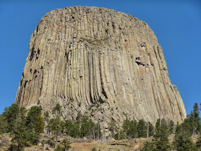 Photo: Behold - Devil's Tower. There is some debate about exactly how the Tower formed. Some think it is the neck of an ancient volcano, others think it is a laccolith, and some think it is a stock (or plug). All three of possibilites are intrusive igneous formations (aka plutonic formations) that form when magma cools beneath the surface. As the magma hardens, it becomes a fairly durable rock that resists erosion better than the sedimentary rock around it. So, after millions of years intrusive formations like Devil's Tower are exposed as the weaker sedimentary rock around them is eroded away.