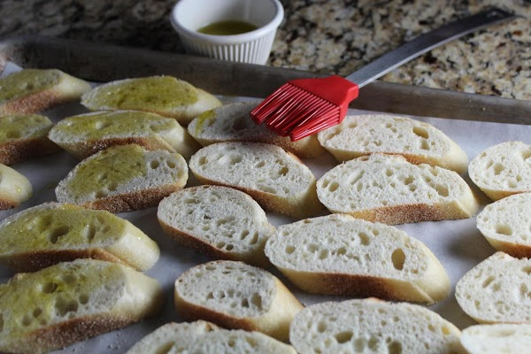 Slice baguettes 1/2 and inch thick. Brush with olive oil and toast in preheated...