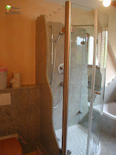Photo: Bei der Planung und Umsetzung dieses Badezimmers haben wir ein Gesamtkonzept erstellt welches  die  Holz-, Granit-, und die Glasarbeiten umfasste. Es entstand ein Podest mit Granitbelag in das die Badewanne versenkt und die bodenebene Dusche aus Granit und Glas eingebaut ist. Zwei Waschtische mit Spiegelüberbau die schräg zueinander angeordnet sind. Und ein WC  in der Nische hinter der Dusche. Als Material haben wir Birnbaum, Kashmir white und Ahorn mit einander kombiniert.