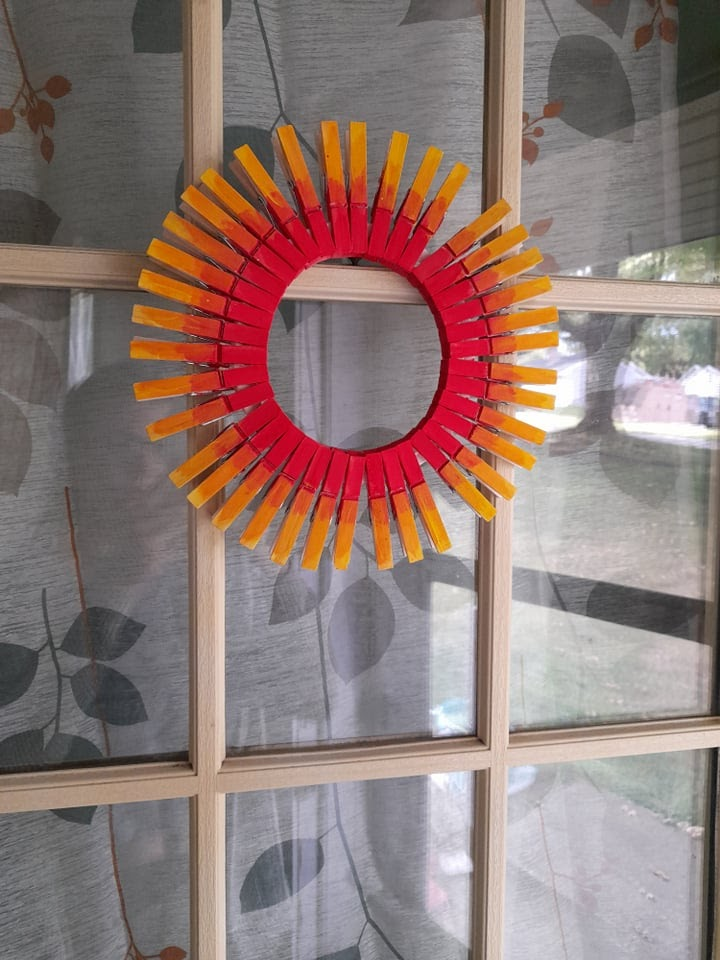 sun clothespin wreath hanging on the front door.