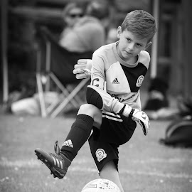 Right in the action by Vix Paine - Babies & Children Children Candids ( caught in the action, goalie, footballer, kick, candid, football, black and white, boy, child )