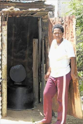 SLOW REMOVALS: A resident of Monyakeng, Wesselsbron in Free State, stands next to her  bucket system toilet.  PHOTO: ANTONIO MUCHAVE