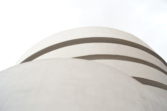 """Photo: """"Flesh and bone...""""  Sometimes the simplicity of a scene is enough to render one speechless before realizing that the perceived simplicity is complex in its own right.  The curves of architecture suggesting a softness usually relegated to flesh against a bone white sky, for example.  —- The architectural design in this photo is the work of Frank Lloyd Wright and is the top of the Solomon R. Guggenheim Museum. Wright was commissioned to design a space for the museum in 1943 and the project took well over a decade to complete. He apparently was disappointed in the choice of New York City as the home of the building as he thought that New York City was overbuilt and overpopulated. However, he complied with the wishes of the client and the Guggenheim was set to be built next to Central Park as possible to keep it as close to nature as possible. It is located on the Upper East Side on 5th Avenue between 88th and 89th Streets across from Central Park.  According to the Guggenheim's site: """"Nature not only provided the museum with a respite from New York's distractions but also leant it inspiration. The Guggenheim Museum is an embodiment of Wright's attempts to render the inherent plasticity of organic forms in architecture.  His inverted ziggurat (a stepped or winding pyramidal temple of Babylonian origin) dispensed with the conventional approach to museum design, which led visitors through a series of interconnected rooms and forced them to retrace their steps when exiting. Instead, Wright whisked people to the top of the building via elevator, and led them downward at a leisurely pace on the gentle slope of a continuous ramp. The galleries were divided like the membranes in citrus fruit, with self-contained yet interdependent sections. The open rotunda afforded viewers the unique possibility of seeing several bays of work on different levels simultaneously. The spiral design recalled a nautilus shell, with continuous spaces flowing freely one into another.""""   New """