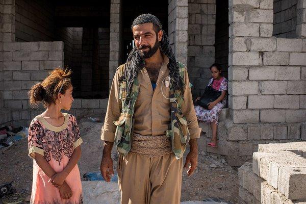 Ако на фоне дома, в который он помог перебраться одной из семей, Туз-Хурмату, Ирак. Фото: Чингис Яр