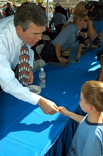 Jeb Bush gives out free Florida quarters to children 18 years of age following an ceremony at the KSC Visitor Complex.