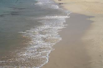 Photo: Man går och njuter på stranden.