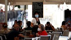 Una camarera con mascarilla atiende a los clientes en una terraza de un bar de Madrid.