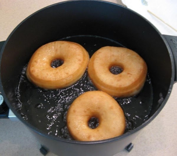 Drop the doughnuts into the hot oil, a few at a time. Turn the...