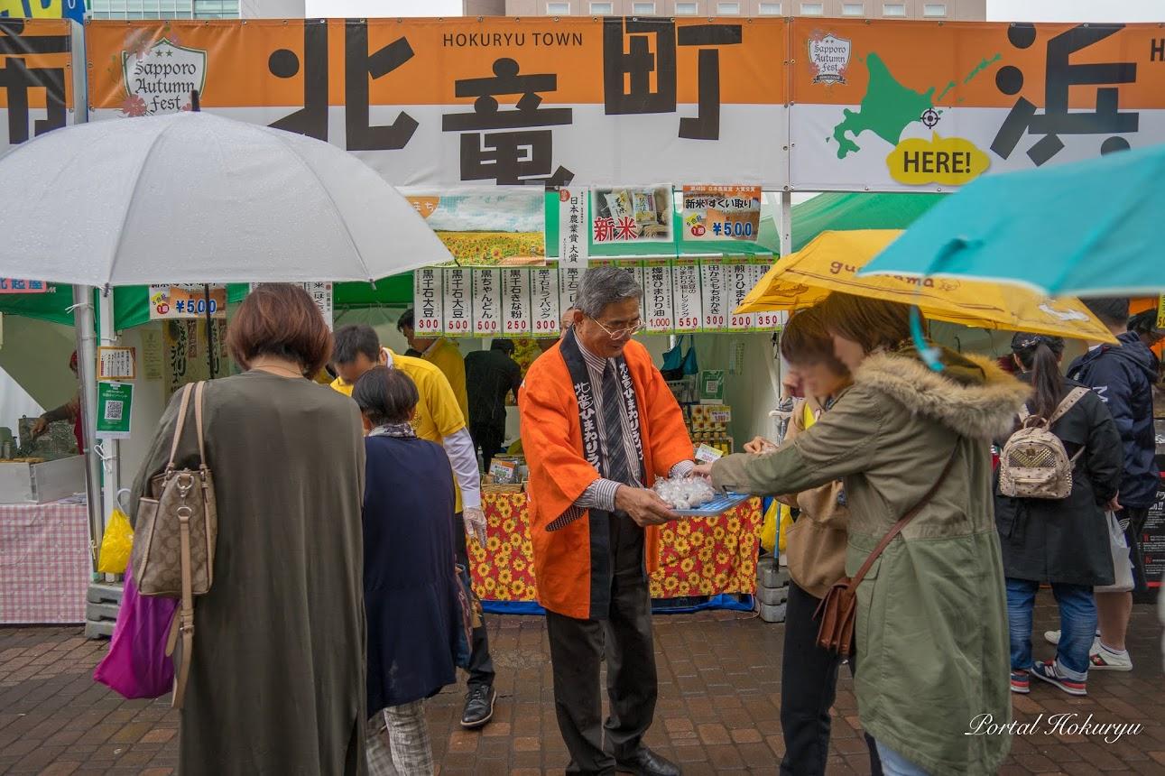 雨降る中、新米ミニおにぎりを勧める佐野町長
