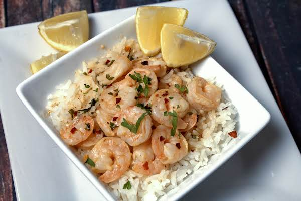 Shrimp Poured Over White Rice And Served With Lemon Wedges.