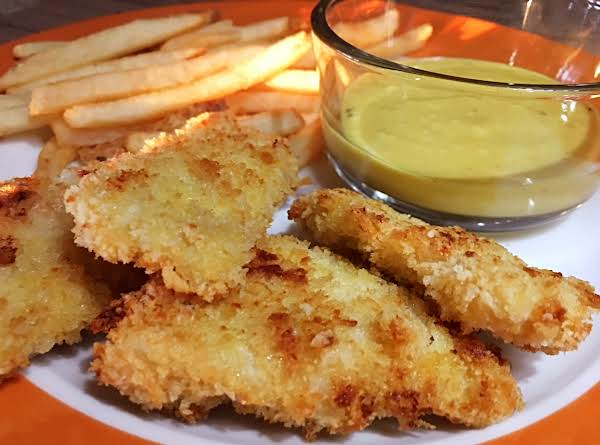 A Few Chicken Fingers With Dipping Sauce In A Small Glass Bowl With French Fries On A White/orange Plate.