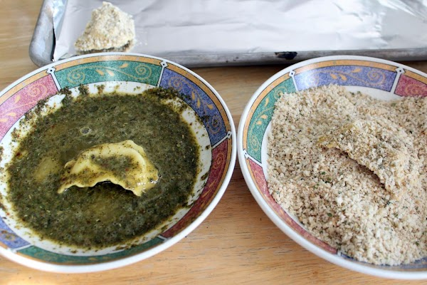 Dredging ravioli in egg and bread crumbs.