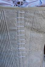 Photo: Corset Midbust Ref.: CRM 1785-90 01 Valor: R$ 600,00 Corset / Stays midbust datado de 1785/90 ( réplica) em brocado gelo. Todo confeccionado com barbatanas de baleia ( sintética). Confeccionado em brocado na camada externa, duas camadas de sarja 100% algodão e uma camada de entretela. São 6 barbatanas flats em aço temperado revestido ou aço inóx e dezenas de barbatanas de baleia ( sintética) ao redor de todo o corset. O valor padrão refere-se às medidas até 89 cm de cintura. Para peças com medidas maiores, entre em contato.  Verifique disponibilidade de modelo, tecidos e cores entrando em contato. O tom pode variar dependendo da calibragem de cor do seu monitor ou celular.  Também disponível nos tecidos e cores: - Brocado bege; - Brocado branco; - Brocado rosa.