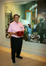 """Photo: Jerry Kaplan stands in front of his painting """"Ode to Picasso"""" by William Haney while holding a set of three nested, red-lacquer bowls by Yoshinari Satake"""