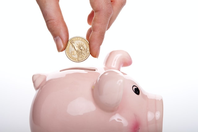 A person depositing coins in a piggy bank to travel for cheap