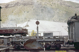 "Photo: 078-14.   Flanger ""OD"" next to ramp to coaling tower bin.  Huge tailings dump is adjacent to the large smelter across the Animas River.  Winds used to blow toxic dust from the tailings all over this part of Durango.  Tailings and smelter have been removed for many years.  7/28/60."