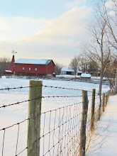 Photo: Snow and sunlight on a barbed wire fence and red barn with windmill at Carriage Hill Metropark in Dayton, Ohio.