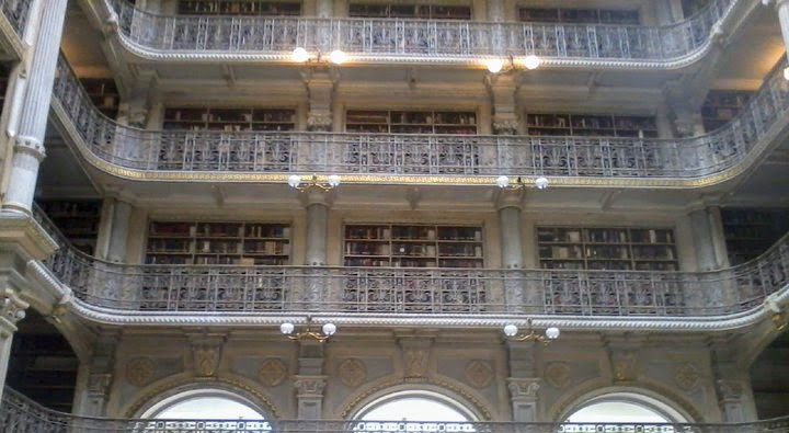 Figure 1: interior of the Peabody Library showing bookshelves and decorative gates surrounding the open floor shelving.