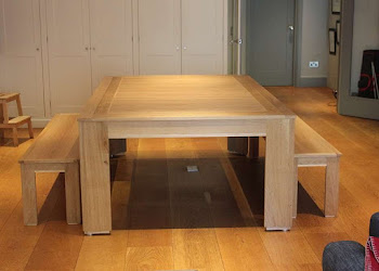 a long light wooden table on wooden flooring