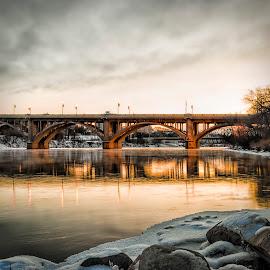 Evening On The Riverbank by Scott Hryciuk - Buildings & Architecture Bridges & Suspended Structures ( canada, rocks, saskatoon, saskatchewan, winter, river, clouds, evening, water )