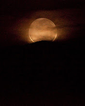 Photo: Setting Crescent  The last sliver of a crescent moon sets over Death Valley.    The round disk is the dark side of the moon; the tips of the crescent are barely visible.