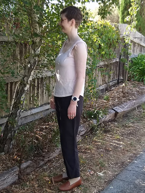 Siobhan stands in front of a tree-lined fence. She wears a pink tank top, black elastic waist straight leg linen pants and brown loafers. She is side on to camera.