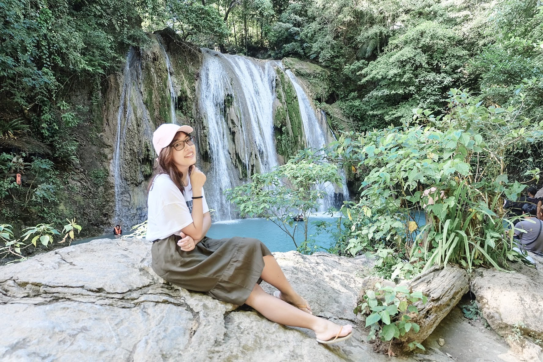 A girl sitting in a rock with Daranak Falls Tanay in her background