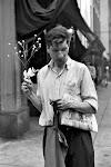 man op straat met krant onder arm en takje met bloemetjes in knop