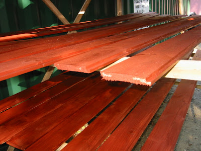 Redwood stained siding against green metal