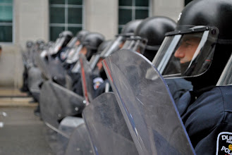 Photo: Riot police form a line to prevent demonstrators from passing them.
