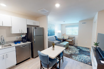 Furnished one bedroom floorplan with white cabinets, stainless steel appliances, and wood-inspired flooring