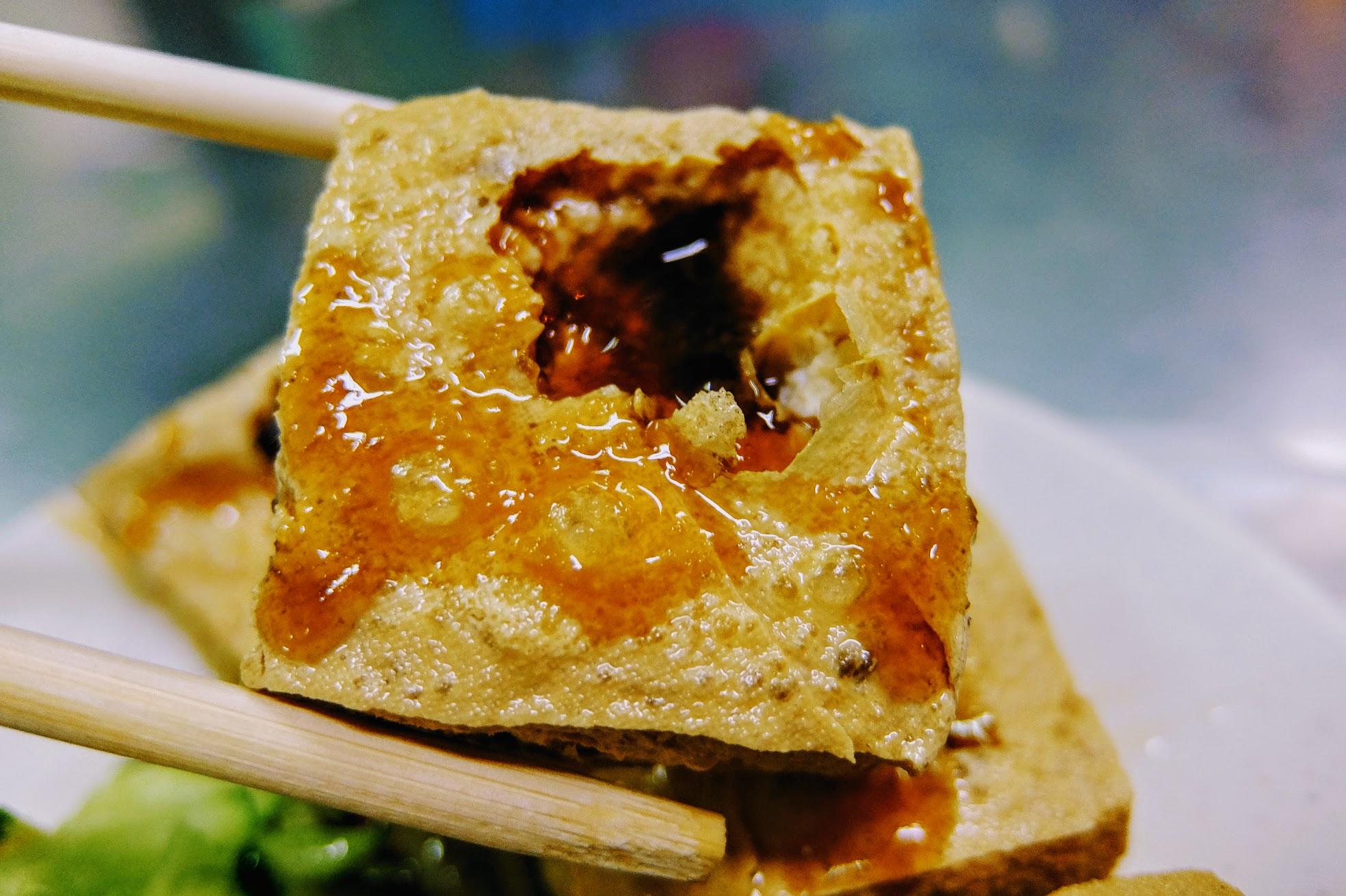 臭豆腐戳洞,淋上蒜蓉醬,再搭配旁邊的黃瓜絲與泡菜,對味!