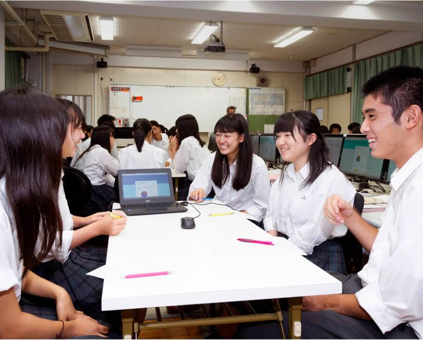 Students in white collaborating at a table 共同学習をする生徒たち
