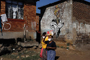 Residents of Kliptown in Soweto carry food donated by photojournalist Ilan Ossendryver. He says he is using the camera as a