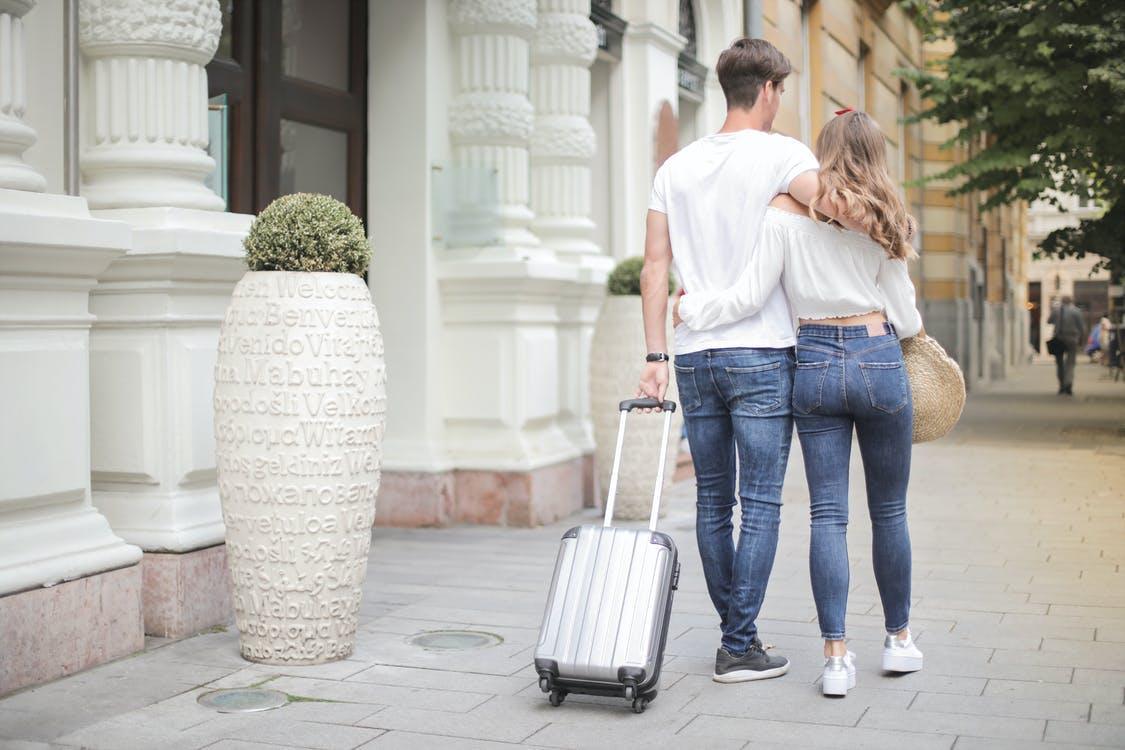 Back view of traveling couple in love wearing casual clothes walking with luggage and hugging while strolling along sidewalk together during vacation
