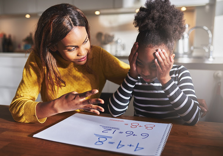 Mother teaching her daughter to calculate elementary school work.