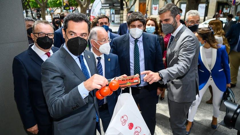 Juanma Moreno adquiriendo una bolsa de tomates solidarios.