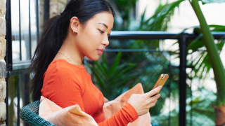 young woman holding smartphone in hand and looking at it