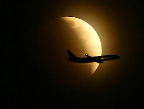Photo: An airplane passes in front of a darkening moon as it becomes a total lunar eclipse on Wednesday, Feb. 20, 2008 in Seattle.  (AP Photo/Joshua Trujillo - Seattle Post-Intelligencer) **MANDATORY CREDIT**