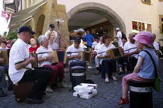 Photo: Unsere kleine  Dirigentin Salome ist etwas ermüdet und geniesst  die  Musik auf dem Randstein.  Am Boden drei Schachteln mit Nidelkuchen. Ein Geschenk der nahegelegenen Bäckerei. Dankschön vielmal!