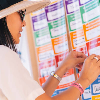 A woman places a sticker with feedback about the plan on a poster board.