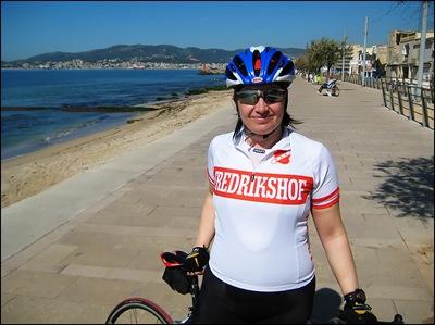 Lycklig cyklist på strandpromenaden