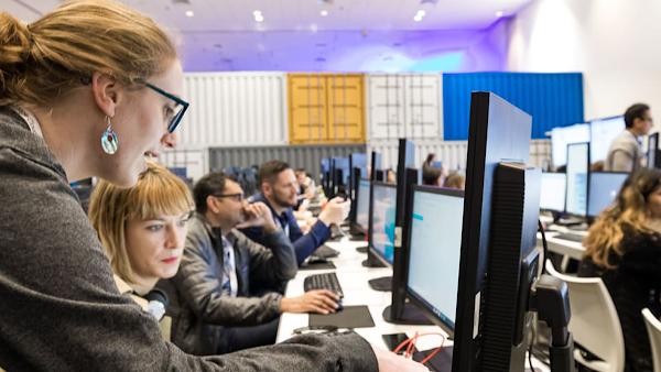 Instrutora mostrando a um aluno como realizar uma tarefa em um computador