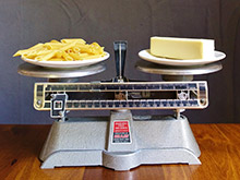 A balance scale with pasta/carbs weighed against butter/fat.