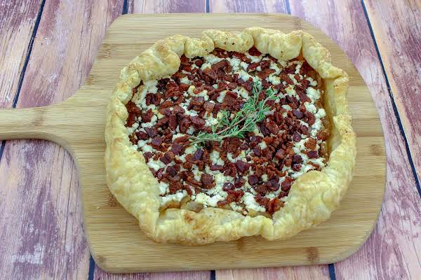 Caramelized Onion And Goat Cheese Tart With A Sprig Of Thyme.