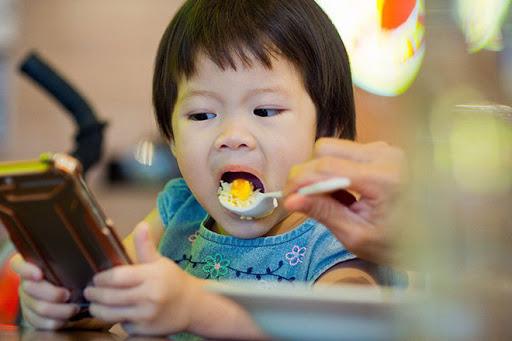 Không nên cho trẻ vừa ăn vừa xem tivi, sử dụng điện thoại hay dong trẻ ăn
