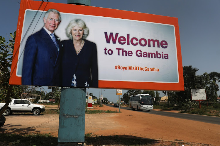 A poster of Britain's Prince Charles, Prince of Wales, and Camilla, Duchess of Cornwall hangs on a street pole ahead of their visit to Banjul, Gambia.